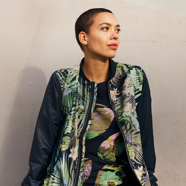 A woman in a bright-coloured jacket standing against a wall