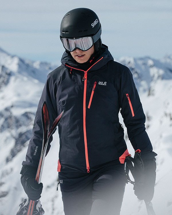 Woman in skiwear and wearing a helmet in front of snow-covered mountains